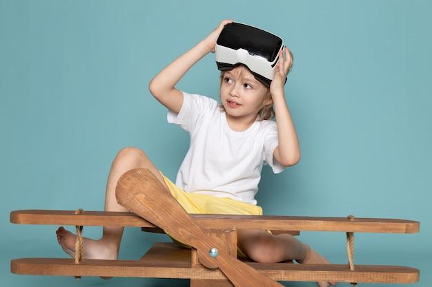 Vista frontal niño lindo jugando gafas vr en camiseta blanca en el piso azul