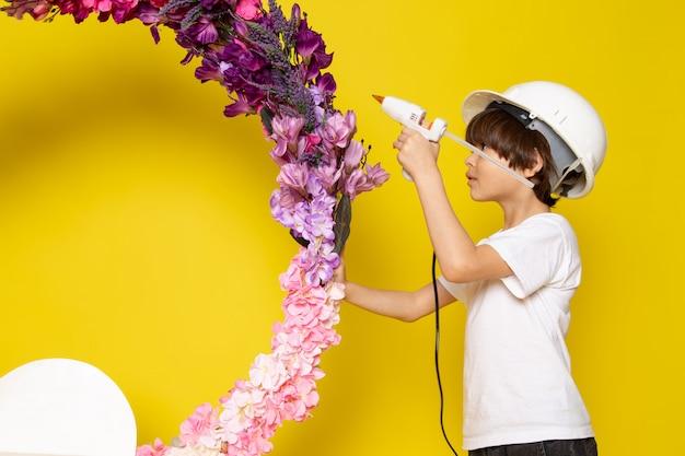 Una vista frontal niño lindo niño en camiseta blanca y casco blanco que adorna el puesto de flores en el escritorio amarillo