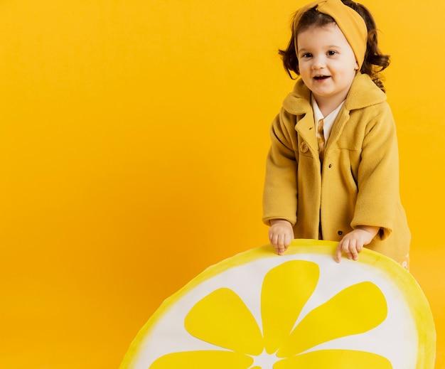 Vista frontal del niño lindo posando con decoración de rodaja de limón