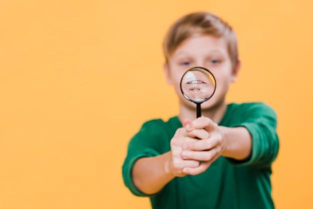 Vista frontal del niño con lupa