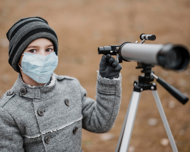 Vista frontal niño con máscara médica con un telescopio