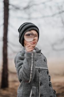Vista frontal niño mirando a través de una lupa