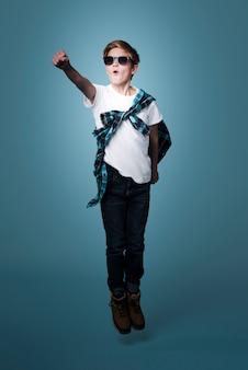 Vista frontal del niño moderno con gafas de sol posando