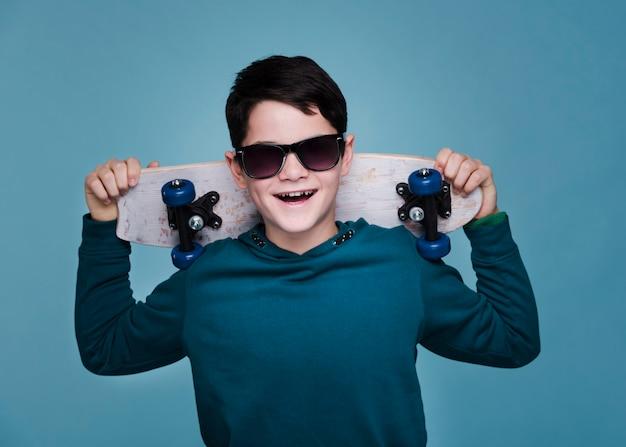 Vista frontal del niño moderno con patineta