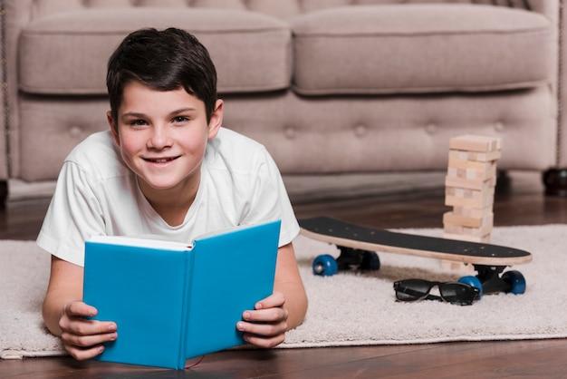Vista frontal del niño moderno sentado en el piso con libro