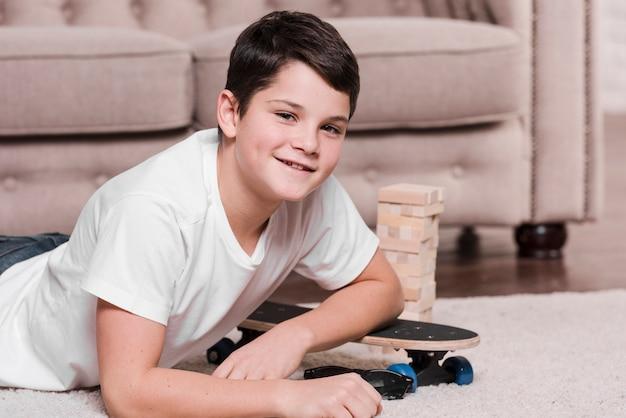 Vista frontal del niño moderno sentado en el piso con patineta