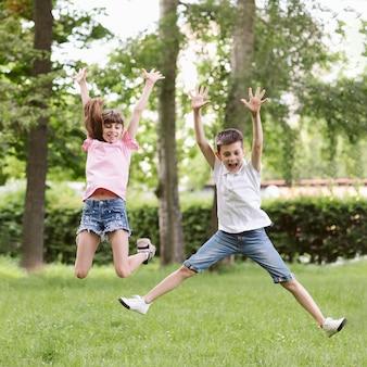Vista frontal niño y niña saltando