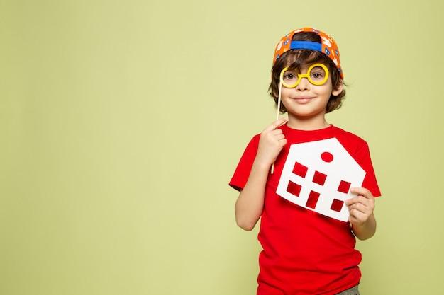 Una vista frontal niño niño adorable en camiseta roja sonriendo con gorra de béisbol en el espacio de color piedra