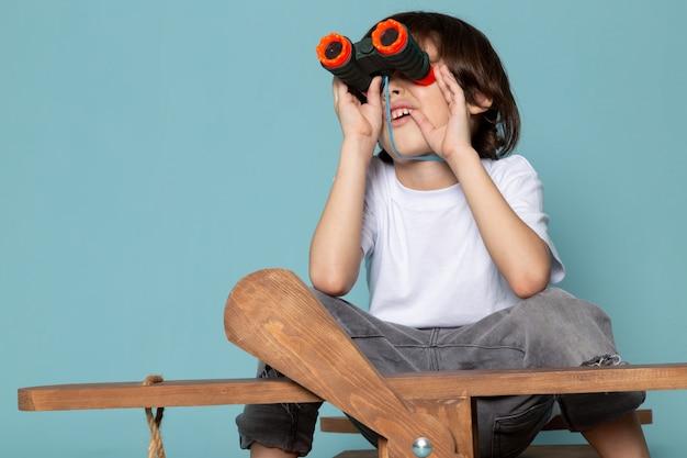 Vista frontal del niño pequeño en camiseta blanca con binoculares en el escritorio azul