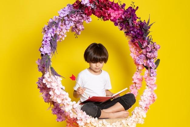 Una vista frontal del niño pequeño en camiseta blanca leyendo el libro sobre la flor hecha soporte en el espacio amarillo