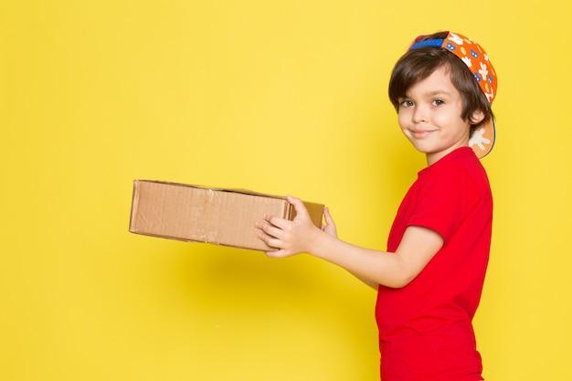 Una vista frontal del niño pequeño en la camiseta roja colorida gorra y pantalón de color caqui con caja en el fondo amarillo