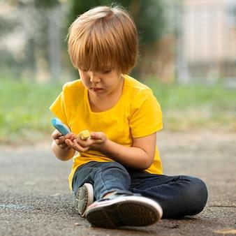 Vista frontal, niño pequeño en el parque de dibujo