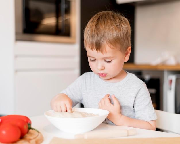 Vista frontal del niño pequeño que cocina en casa