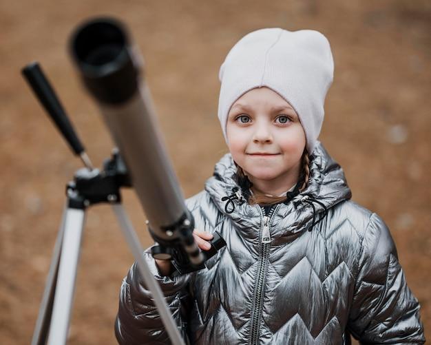 Vista frontal del niño pequeño con un telescopio