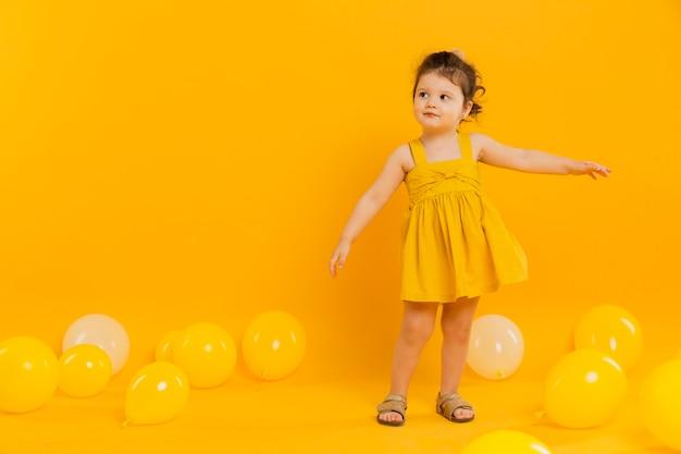 Vista frontal del niño posando con globos y espacio de copia