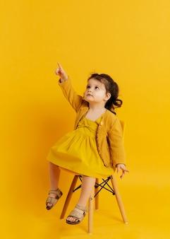 Vista frontal del niño posando mientras está sentado en la silla y apuntando hacia arriba