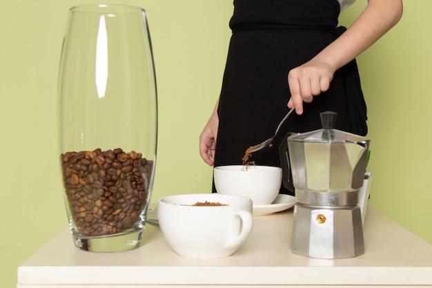 Una vista frontal niño preparando café en la mesa