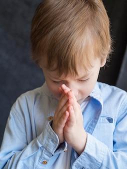 Vista frontal del niño rezando