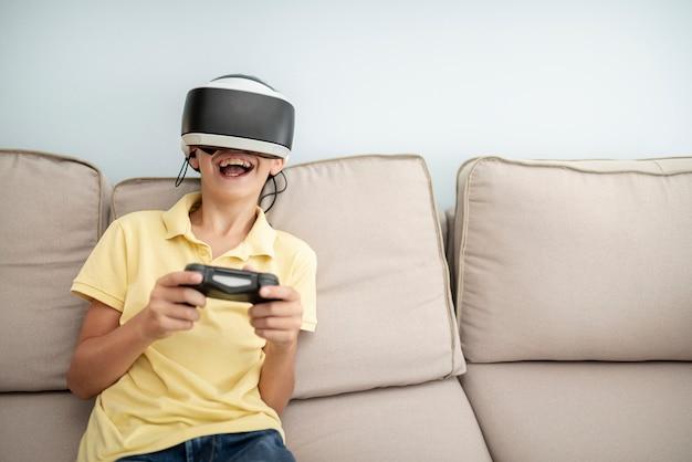 Vista frontal niño riendo jugando con gafas vr