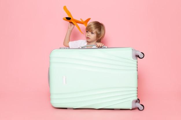 Vista frontal niño rubio con avión naranja sobre el escritorio rosa