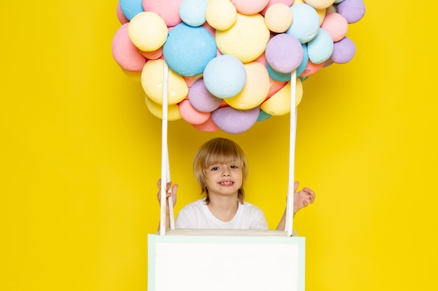 Vista frontal niño rubio en camiseta blanca junto con coloridos globos de aire en el amarillo