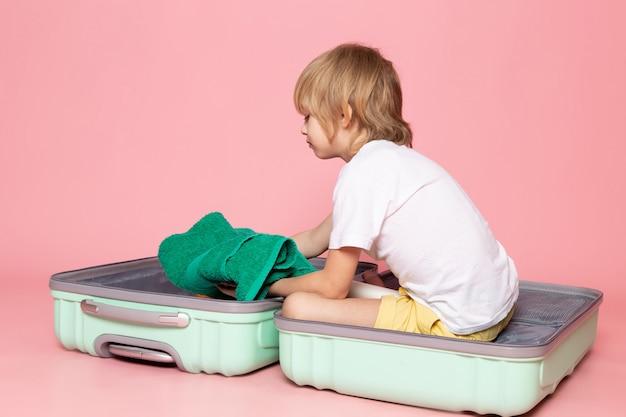 Vista frontal del niño rubio dentro de la bolsa azul en rosa
