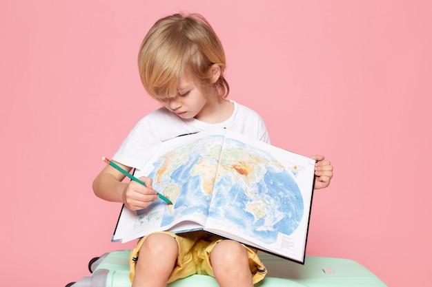 Vista frontal del niño rubio dibujando mapa en camiseta blanca en escritorio rosa