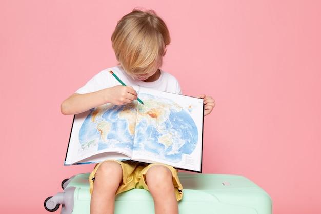 Vista frontal del niño rubio dibujo mapa en camiseta blanca sobre rosa