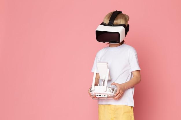 Una vista frontal niño rubio jugando vr en camiseta blanca y jeans amarillos en el espacio rosa