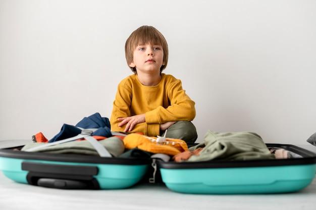 Vista frontal del niño sentado junto al equipaje en casa