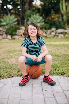 Vista frontal del niño sentado en la pelota