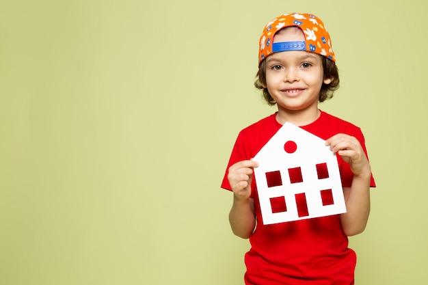 Una vista frontal niño sonriente en camiseta roja y gorra de béisbol en el espacio de color piedra