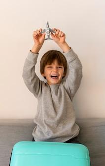 Vista frontal del niño sonriente con equipaje y figurilla de avión