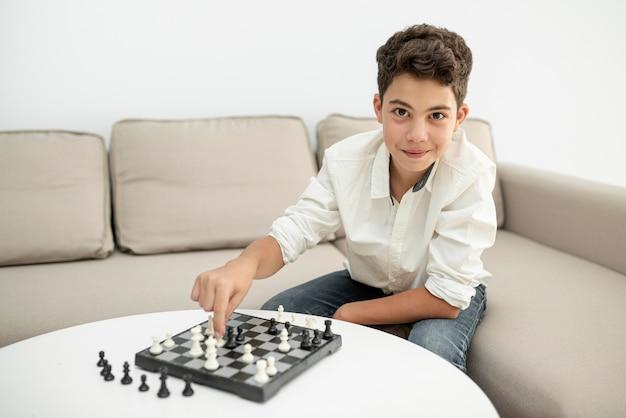 Vista frontal niño sonriente jugando al ajedrez