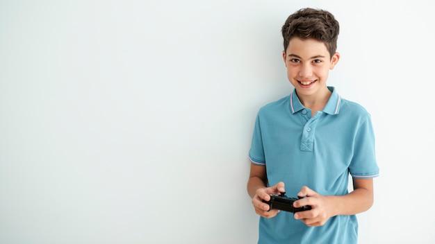 Vista frontal niño sonriente jugando con un controlador