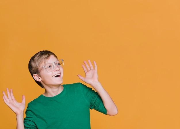 Vista frontal del niño sonriente mirando a otro lado con espacio de copia