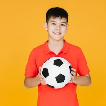 Vista frontal niño sonriente sosteniendo una pelota de fútbol