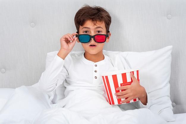 Vista frontal niño sorprendido mientras ve la película