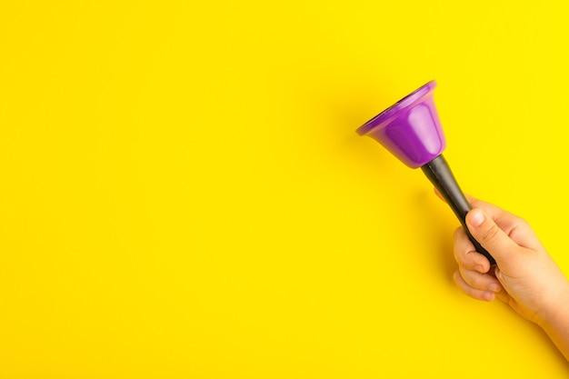 Vista frontal niño sosteniendo campana púrpura sobre superficie amarilla