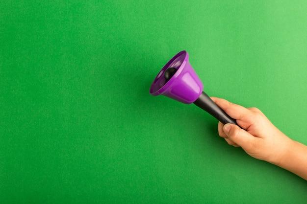 Vista frontal niño sosteniendo campana púrpura sobre la superficie verde