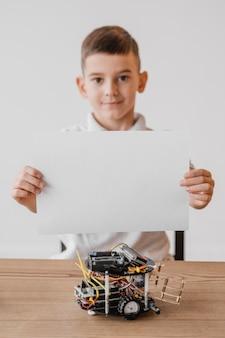Vista frontal niño sosteniendo un libro blanco