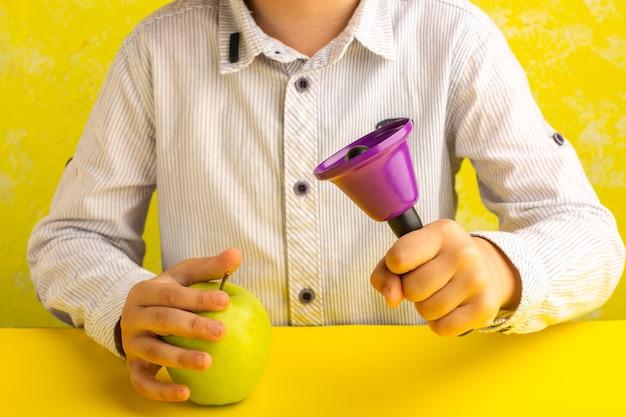 Vista frontal niño sosteniendo manzana verde y campana púrpura sobre superficie amarilla