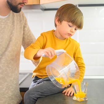 Vista frontal niño vertiendo jugo de naranja en vaso