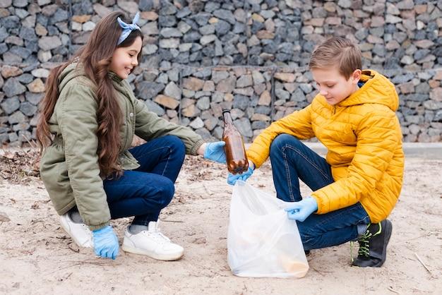 Vista frontal de niños con bolsas de plástico
