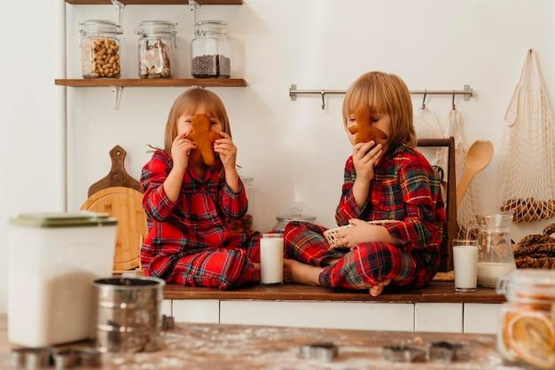 Vista frontal de los niños comiendo galletas juntos el día de navidad