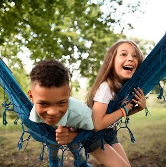 Vista frontal de niños felices en hamaca
