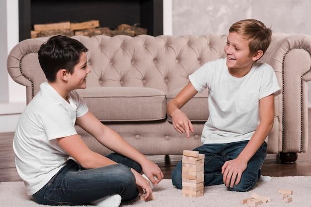 Vista frontal de niños jugando un juego en el piso