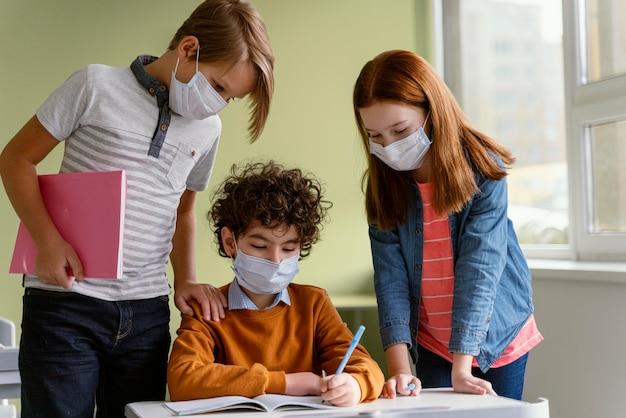 Vista frontal de niños con máscaras médicas aprendiendo en la escuela