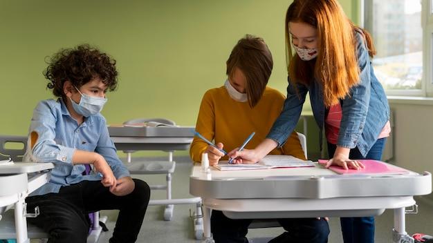 Vista frontal de los niños con máscaras médicas en la escuela asistiendo a clases