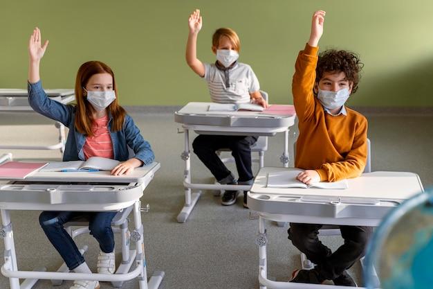 Vista frontal de los niños con máscaras médicas en la escuela levantando sus manos